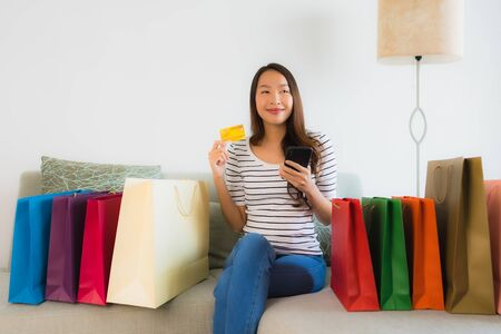Portrait beautiful young asian women with credit card mobile phone or computer for online shopping on sofa in living room interior Banco de Imagens - 135533660