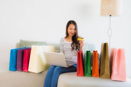Portrait beautiful young asian women with credit card mobile phone or computer for online shopping on sofa in living room interior Banco de Imagens