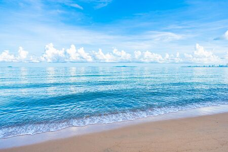Beautiful tropical beach sea ocean with white cloud blue sky and copyspace for leisure travel in holiday vacation concept Imagens