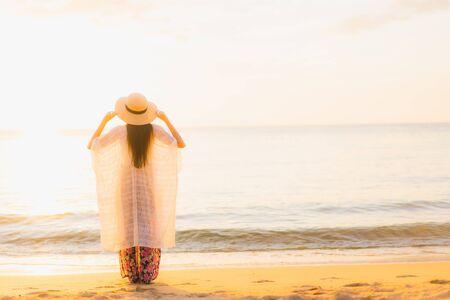 Il sorriso felice delle belle giovani donne asiatiche del ritratto si rilassa intorno all'oceano del mare della spiaggia al tramonto o all'ora dell'alba per le vacanze di viaggio Archivio Fotografico