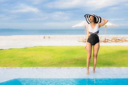 Portrait beautiful young asian women happy smile relax around swimming pool near sea beach ocean in hotel resort