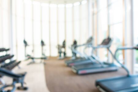 Abstract blur gym room interior with fitness equipment for background