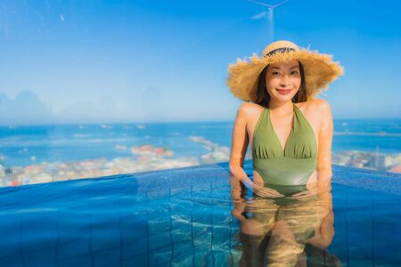 Beautiful young asian women happy smile relax around outdoor swimming pool in hotel resort neary sea beach for travel in holiday vacation