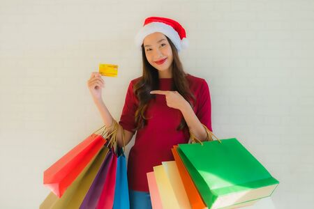 Portrait beautiful young asian women wear christmas santa hat with shopping bag smart mobile phone and credit card