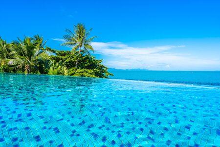 Piękny luksusowy odkryty basen w kurorcie hotelowym z oceanem morskim wokół palmy kokosowej i białą chmurą na niebieskim niebie na wakacyjne podróże