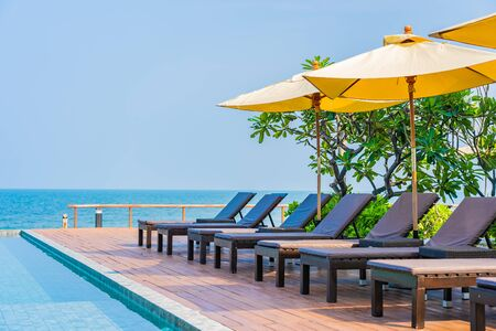 Beautiful empty chair umbrella around outdoor swimming pool in hotel resort for travel vacation