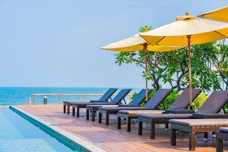 Bellissimo ombrellone vuoto intorno alla piscina all'aperto nel resort dell'hotel per le vacanze di viaggio