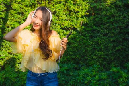 Young asian woman using smart mobile phone with headphone for listen music around outdoor garden nature view Stock Photo