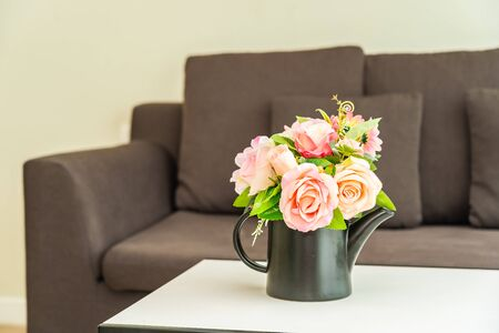 Vase flower on table with pillow and sofa decoration interior of living room area Archivio Fotografico