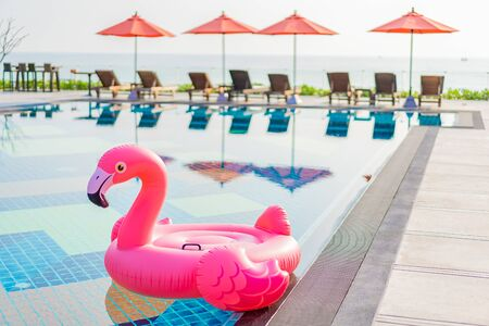 Flamingo float around swimming pool in hotel resort with umbrella and chair in hotel resort for travel vacation