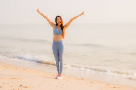 Portrait sport young asian woman prepare exercise or run on the beach sea ocean for health