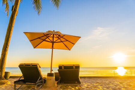 Beautiful tropical nature umbrella chair with palm tree around beach sea ocean at sunset or sunrise for travel vacation