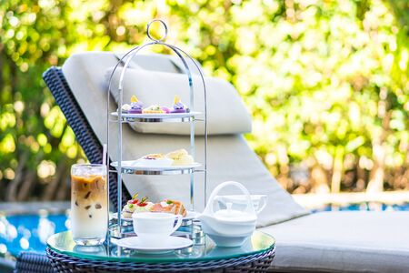 Afternoon tea set with latte coffee and hot tea on table neary chair around swimming pool in hotel resort