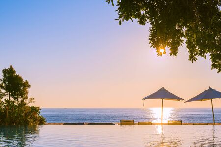 Beautiful tropical outdoor beach sea ocean with umbrella and chiar around outdoor swimming pool at sunset or sunrise time for travel vacation Stockfoto