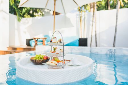 Breakfast and afternoon tea set floating around swimming pool in hotel resort Stock Photo