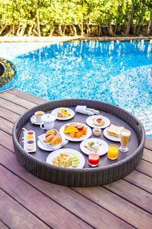Flotaing breakfast tray around outdoor swimming pool with bread fruit egg coffee cup and juice