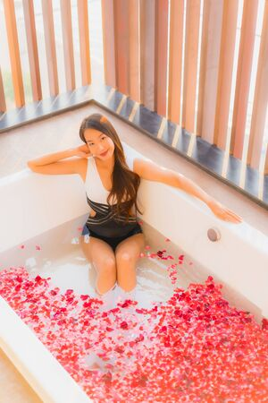Portrait beautiful young asian woman happy smile relex in bathtub with rose flower for spa concept