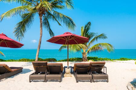 Beautiful tropical beach sea ocean with umbrella and chair around coconut palm tree on blue sky for leisure vacation