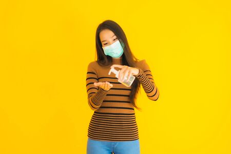 Portrait beautiful young asian woman with mask alcohol spray and gel bottle in her hand for protect from coronavirus or covid19 on yellow isolated background