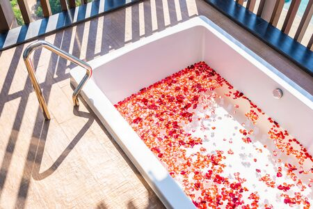 Red rose flower on water in bathtub decoration interior for take a bath and relax