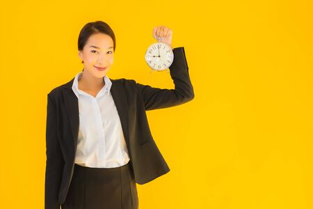 Portrait beautiful young asian woman show time of clock or alarm on yellow isolated background