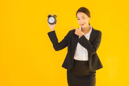 Portrait beautiful young asian woman show time of clock or alarm on yellow isolated background Foto de archivo