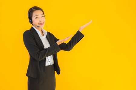 Portrait beautiful young business asian woman with headphone or headset for call center or telemarketing on yellow isolated background Stock Photo