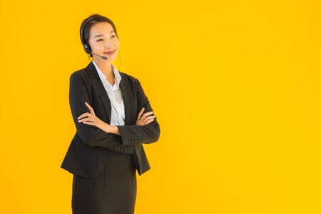 Portrait beautiful young business asian woman with headphone or headset for call center or telemarketing on yellow isolated background