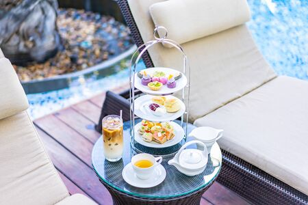 Afternoon tea set with latte coffee and hot tea on table neary chair around swimming pool in hotel resort Stock Photo