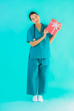 Portrait beautiful young asian doctor woman show red gift box on blue isolated background