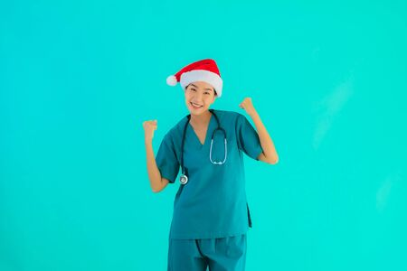 Portrait beautiful young asian doctor woman wear christmas hat with smile happy on blue isolated background Stock Photo