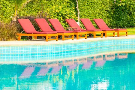 Beautiful empty chair around outdoor swimming pool in hotel resort for travel vacation