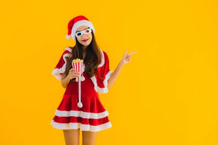Portrait beautiful young asian woman wear christmas clothes hat with popcorn and 3d glasses ready for watch movie on yellow isolated background