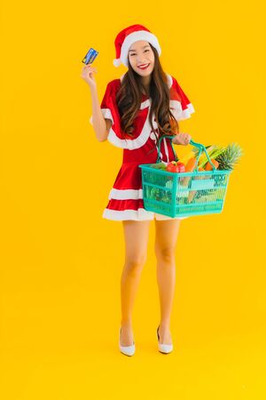Portrait beautiful young asian woman wear christmas clothes hat with grocery basket shopping bag from supermarket store on yellow isolated background
