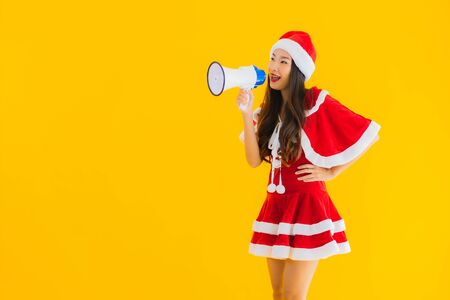 Portrait beautiful young asian woman wear christmas clothes and hat use megaphone on yellow isolated background