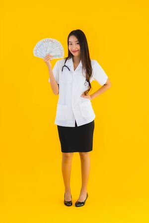 Portrait beautiful young asian doctor woman show cash or money on yellow isolated background