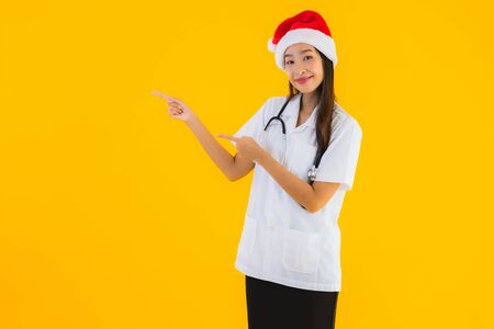 Portrait beautiful young asian doctor woman wear christmas or santa hat on yellow isolated background