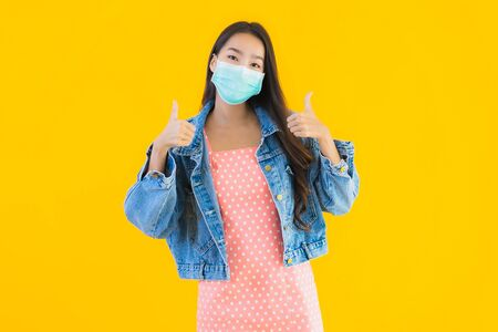 Portrait beautiful young asian woman wear mask for protect coronavirus or covid19 on yellow isolated background