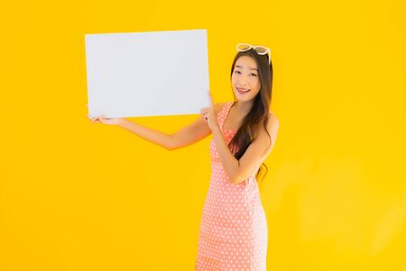 Portrait beautiful young asian woman show empty white billboard for text and copyspace on yellow isolated background Imagens