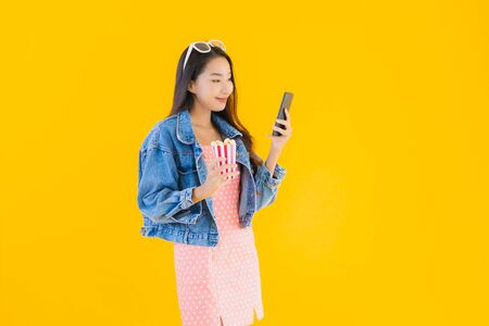 Portrait beautiful young asian woman enjoy happy with phone popcorn and watch movie on yellow isolated background