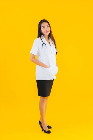 Portrait beautiful young asian doctor woman smile happy work in hospital and clinic on yellow isolated background