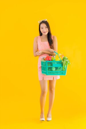 Portrait beautiful young asian woman with grocery in basket shopping from supermarket on yellow isolated background