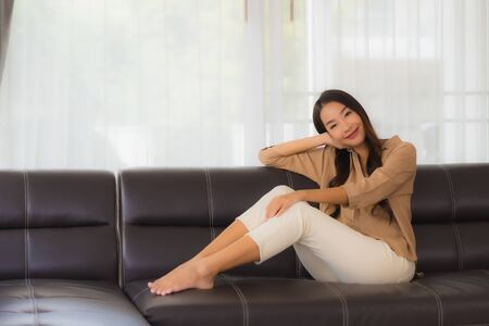 Portrait beautiful young asian woman happy smile relax on sofa in living room interior Banque d'images