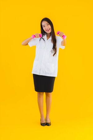 Portrait beautiful young asian doctor woman exercise with dumbbell on yellow isolated background Stok Fotoğraf