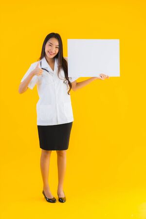 Portrait beautiful young asian doctor woman with empty white board on yellow isolated background 스톡 콘텐츠
