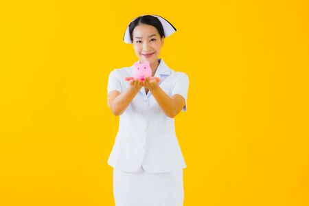 Portrait beautiful young asian woman thai nurse with a lot of cash and money and pink piggy bank on yellow isolated background