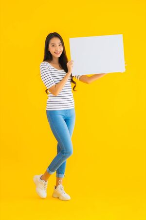 Portrait beautiful young asian woman show empty white billboard sign on yellow isolated background