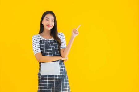 Portrait beautiful young asian woman wear apron with smile happy on yellow isolated background