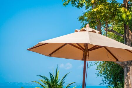 Umbrella and chair around sea beach ocean with coconut palm tree on blue sky background for leisure vacation