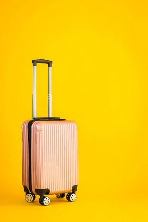 Pink color luggage or baggage bag use for transportation travel and leisure on yellow isolated background